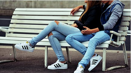 Two friends cuddling on a bench