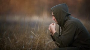 Boy in a field thinking about suicide