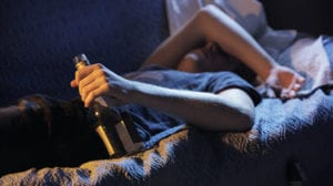 guy-with-a-bottle-of-alcohol-laying-on-a-bed-trying-to-stay-clean-from-addiction