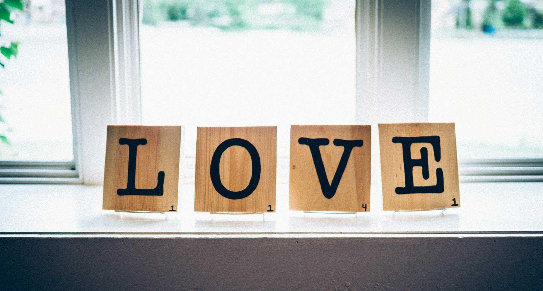 scrabble tiles that spell love on a window sill