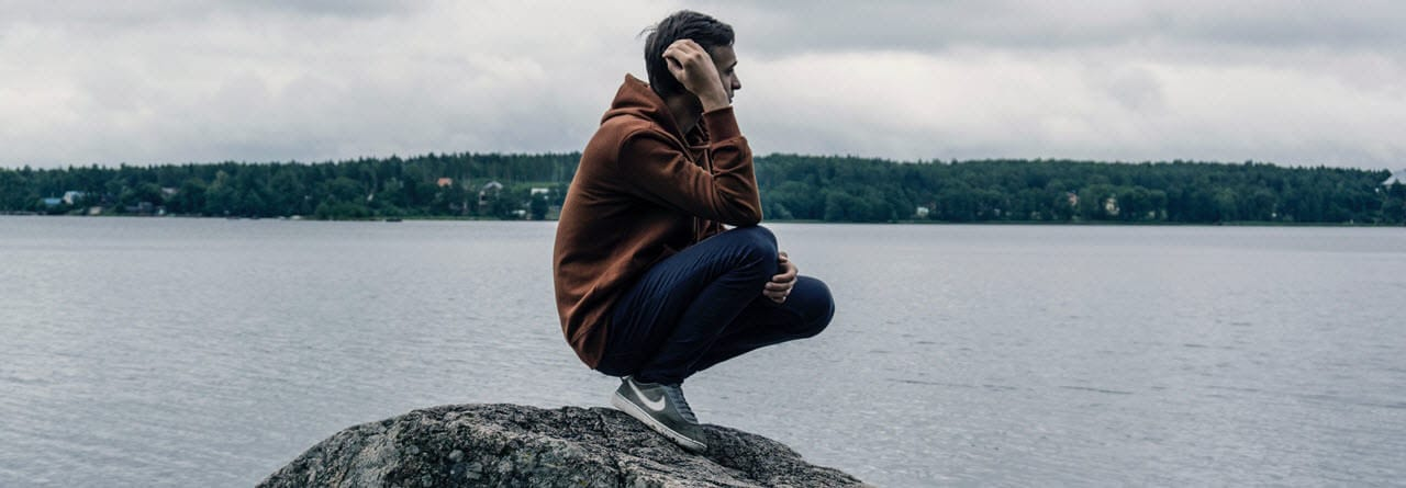 Boy standing on a rock contemplating suicide