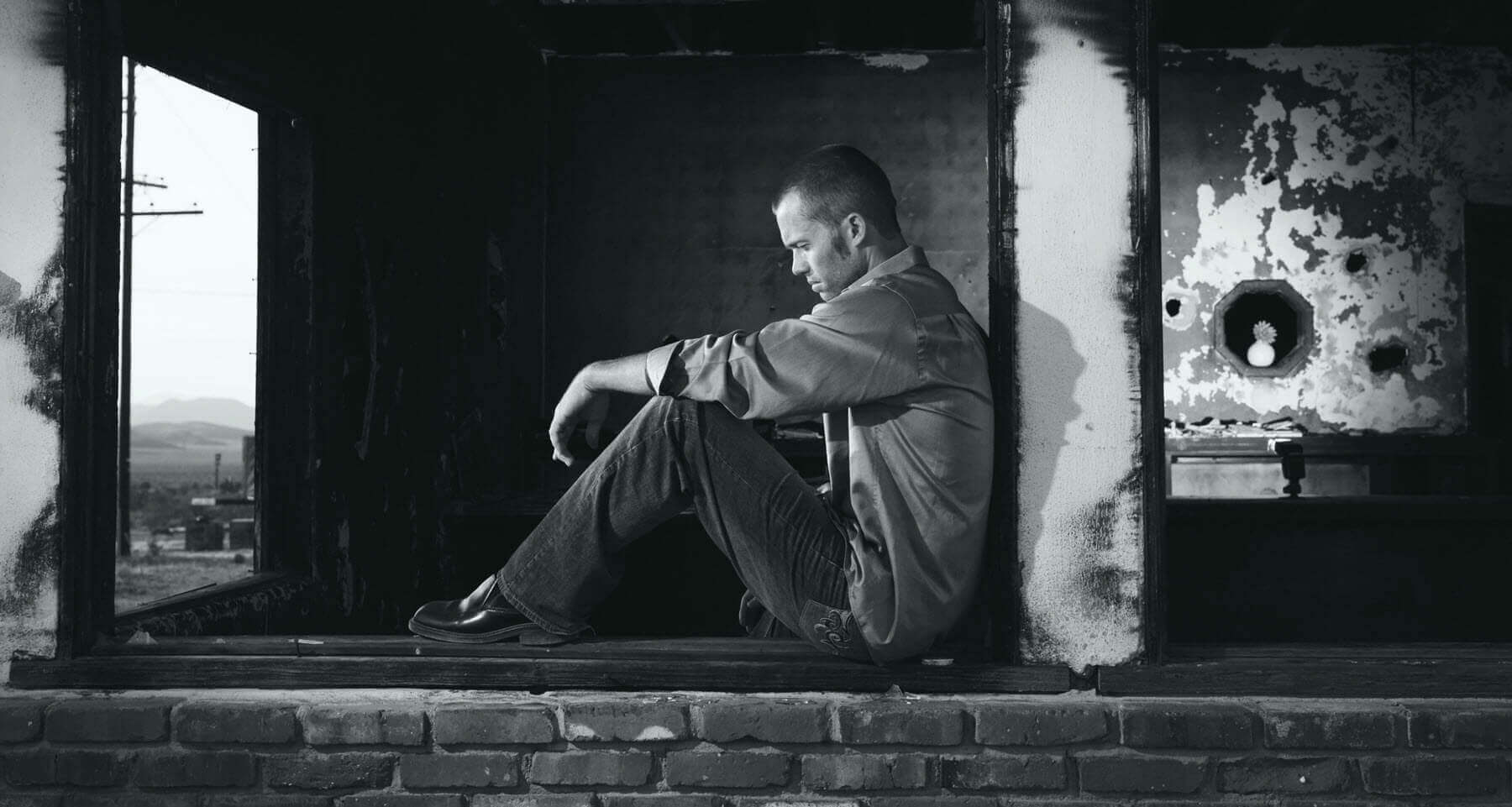 Guy leaning against a wall looking down depressed