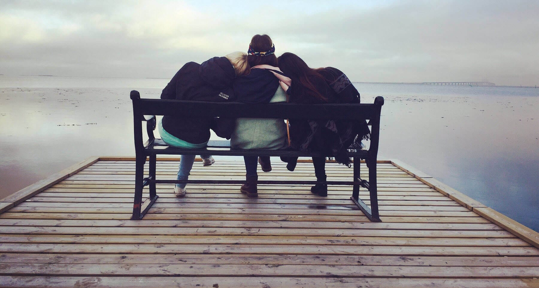 Girls sitting on a bench helping their friend who is struggling with depression