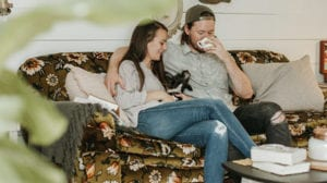 healthy relationship between a couple sitting on sofa with their dog