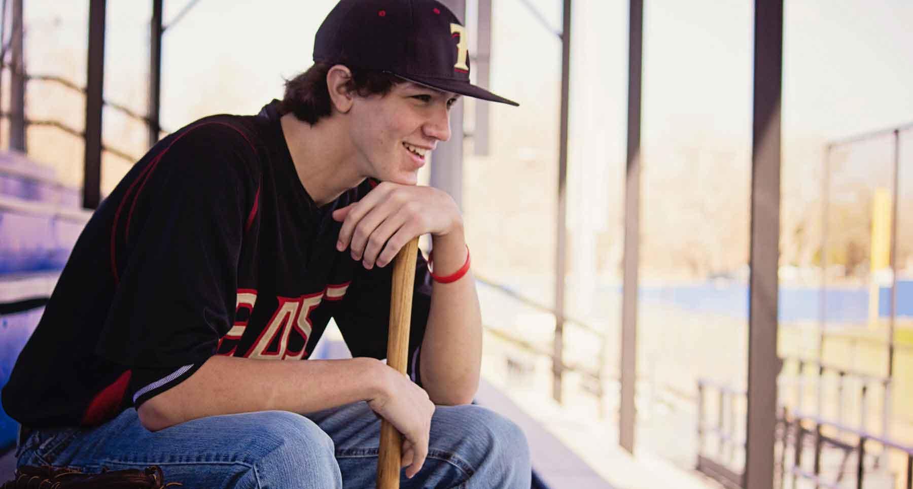 High school guy that plays baseball holding a bat