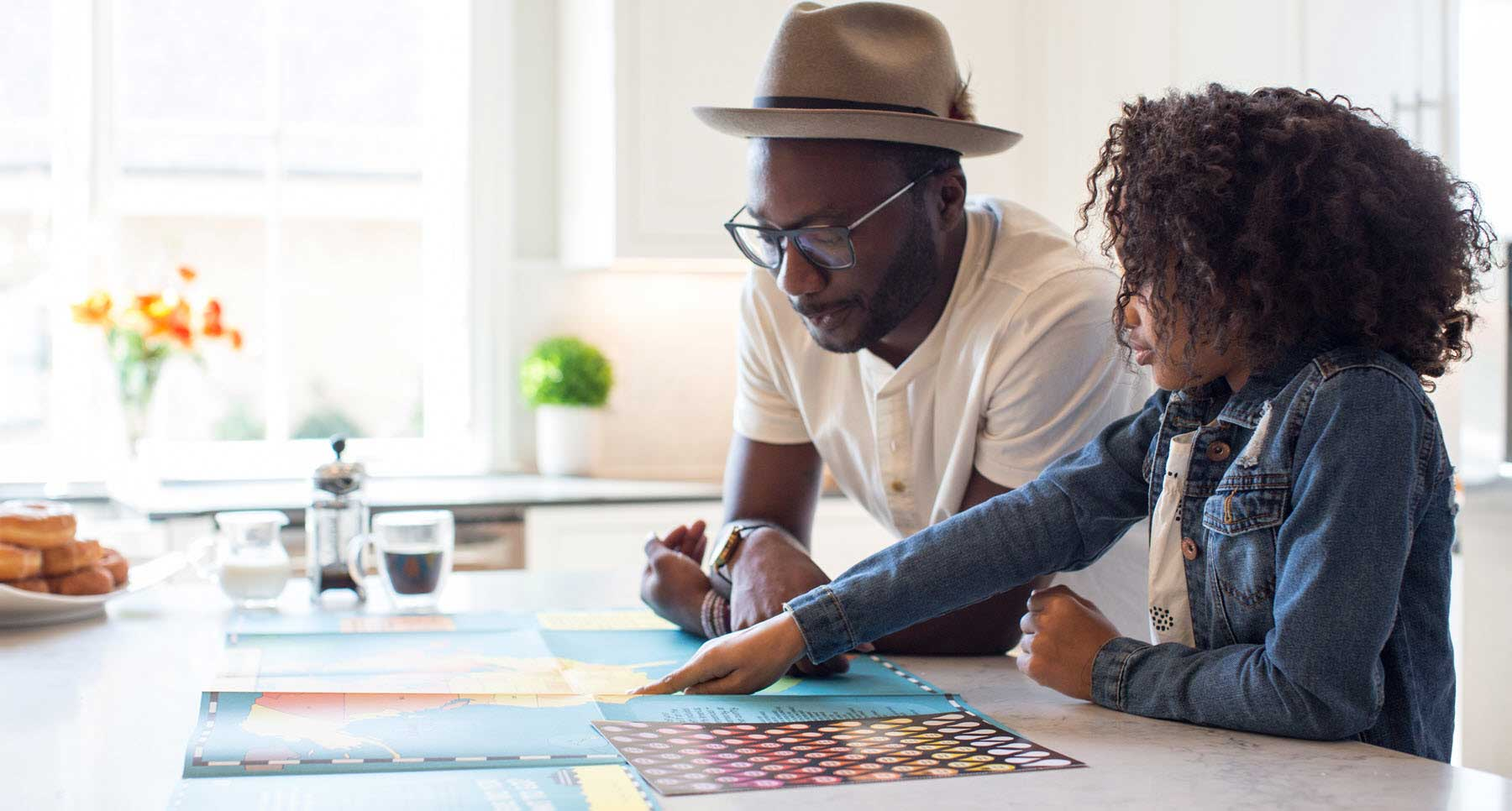 father and daughter looking at a map of the world