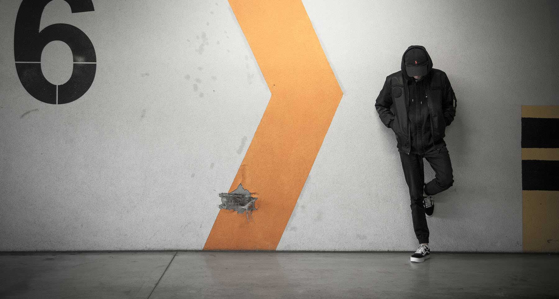 guy standing alone with his head down leaning against a wall