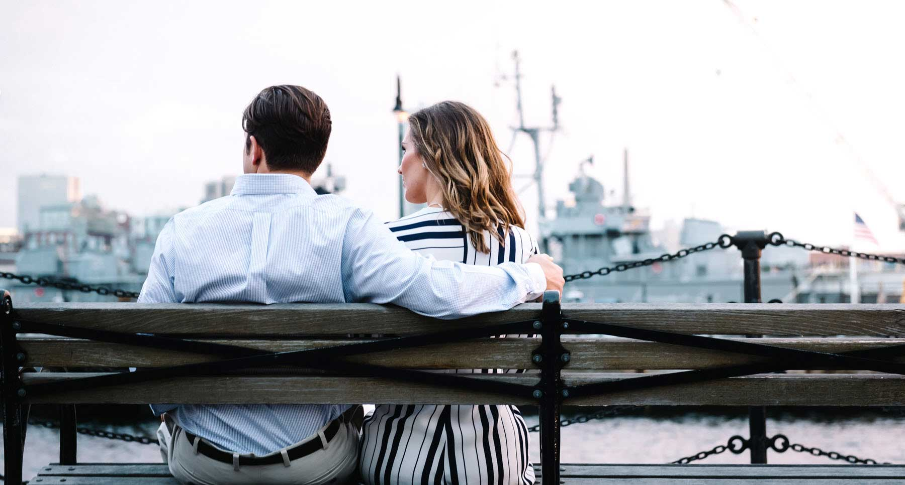 couple sitting solemnly on a bench wondering if they should get back together