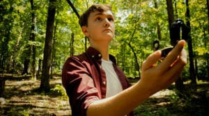 Man in the woods with a compass