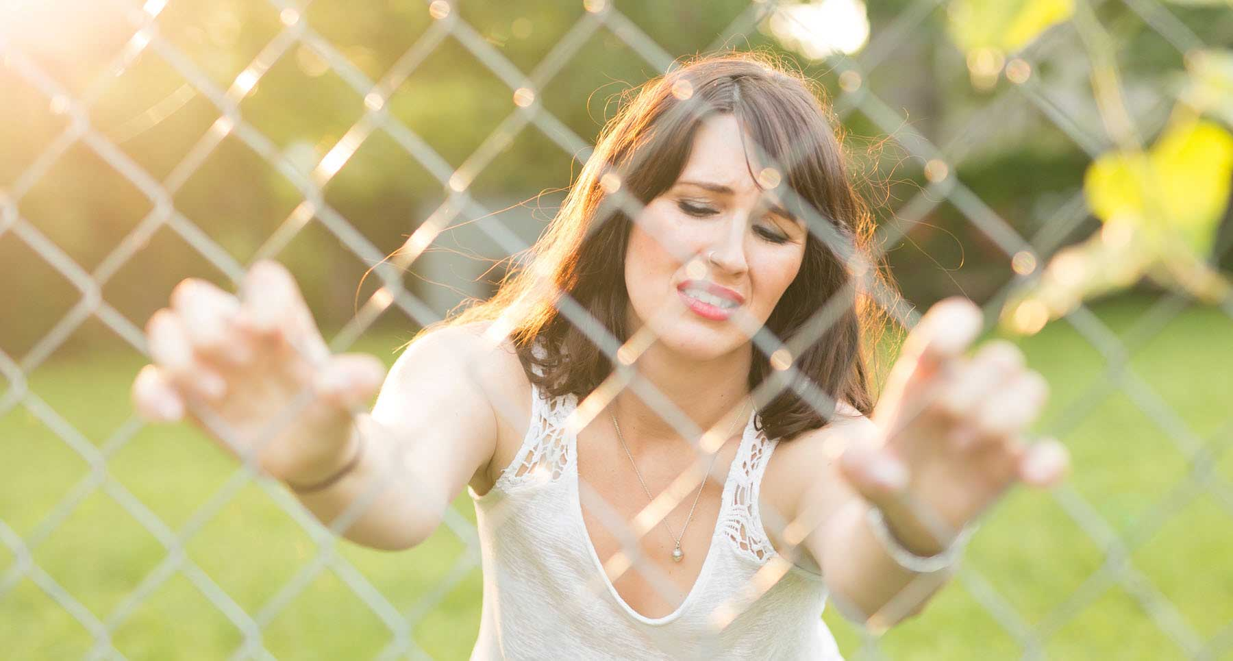woman-holding-on-to-a-chain-link-fence-wanting-to-recover-after-leaving-an-abusive-relationship