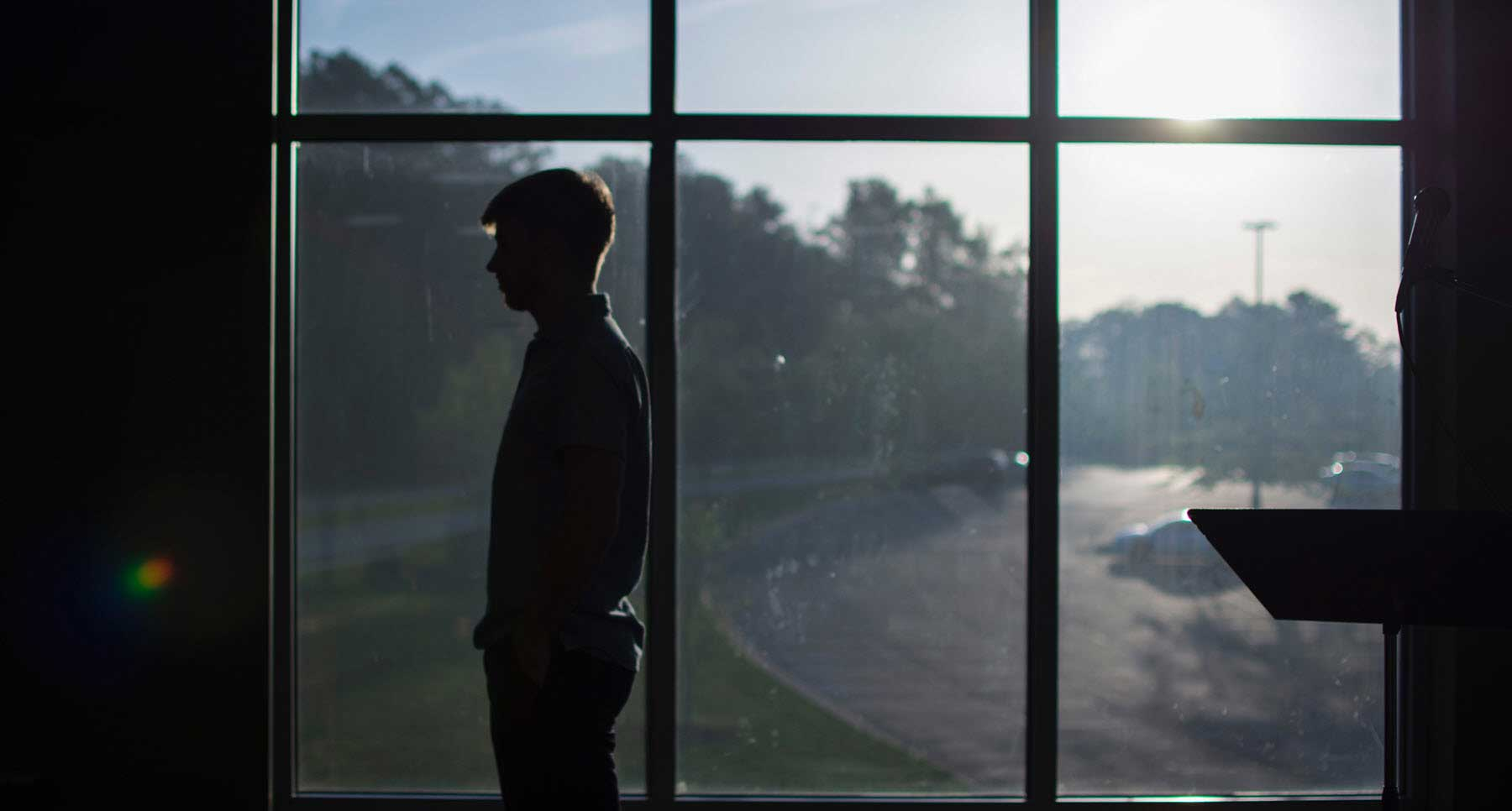 silhouette of a guy-standing-by-a-window-suicide-survivor-learned-lessons-thehopeline-resources