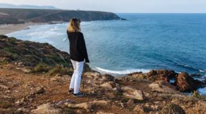 Teen girl looking out at the ocean while uncertain