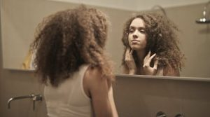 Girl looking in the mirror obsessively
