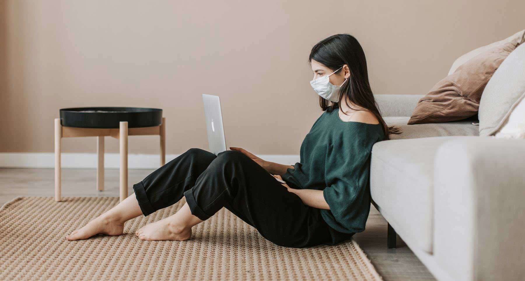 The-World-Is-On-Fire-the--insane-paradox-Millennial-Woman-wearing-a-mask-working-at-home-on-the-computer-dealing-with-pandemic-anxiety-TheHopeLine
