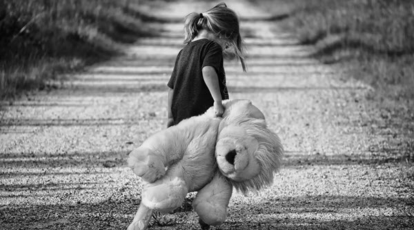 PTSD Post Traumatic Stress Disorder From Childhood Trauma TheHopeLine Young Girl holding a stuffed bear outside alone