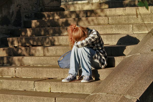 Girl sitting outside at school head down Bullying Living in fear TheHopeLine